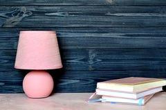 Розовые настольная лампа и книги на столе Стоковое Изображение