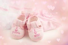 Розовые добычи младенца на яркой розовой предпосылке Одежда младенца Стоковая Фотография RF
