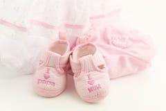 Розовые добычи младенца на яркой розовой предпосылке Одежда младенца Стоковые Фото