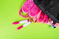 Розовые одежды и аксессуары для фитнеса, бутылка воды, в спорт кладут в мешки, на салатовой предпосылке стоковые фотографии rf