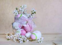Розовые пасхальные яйца в стеклянной вазе с розовыми цветками ленты и вишни Стоковые Фото