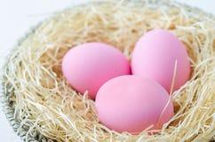 Розовые пасхальные яйца на деревянных шерстях и корзине Стоковая Фотография