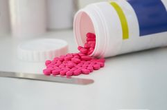 Розовые пилюльки или выплеск таблетки вне от пластичного опарника бутылки с голубым Стоковая Фотография