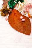 Розовые пилюльки формы шарика на оранжевых лист Стоковая Фотография