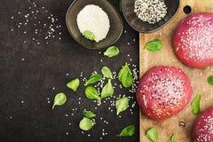 Розовые плюшки для vegetable бургера на основании свеклы с семенами сезама на темной предпосылке Взгляд сверху Стоковое фото RF