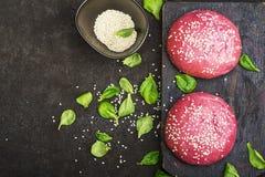 Розовые плюшки для vegetable бургера на основании свеклы с семенами сезама на темной предпосылке Взгляд сверху Стоковая Фотография