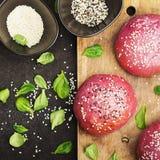 Розовые плюшки для vegetable бургера на основании свеклы с семенами сезама на темной предпосылке Взгляд сверху Стоковая Фотография RF