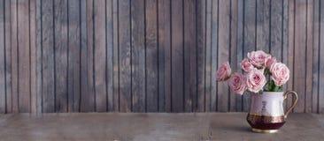 Розовые розы в винтажном кувшине Стоковая Фотография