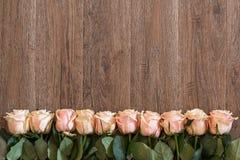 Розовые розы лежа на деревянной предпосылке Предпосылка для тем весны Стоковая Фотография