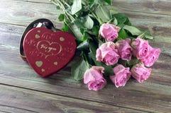 Розовые розы и коробка с помадками на деревянном столе Стоковая Фотография RF