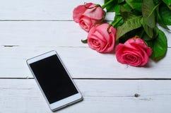Розовые розы и smartphone на деревянной белой предпосылке Стоковые Изображения RF