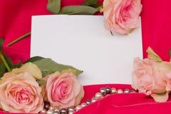Розовые розы с стренгой перл и пустой карточкой Стоковое Изображение