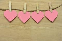 Розовые сердца с деревянными струбцинами и струбциной Висеть на деревянном Стоковые Изображения