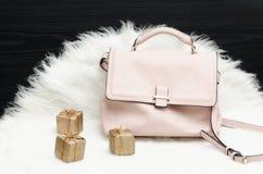 Розовые сумка и подарочная коробка на белом мехе, черной таблице Модный жулик Стоковые Фотографии RF