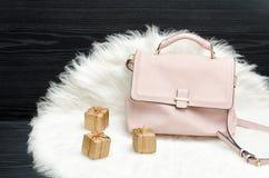 Розовые сумка и подарочная коробка на белом мехе, черной таблице Модный жулик Стоковое Фото