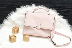 Розовые сумка и подарочная коробка на белом мехе, черной таблице Модный жулик Стоковое Изображение RF