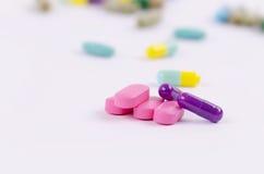 Розовые таблетки и фиолетовые капсулы Стоковое Изображение