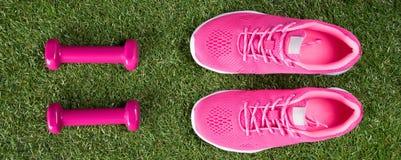 Розовые тапки и гантели для практикуя фитнеса на зеленой лужайке, длинном следе Стоковое Изображение RF