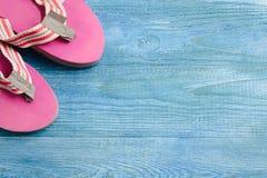 Розовые тапочки на голубой деревянной предпосылке, предпосылке лета и стоковые изображения