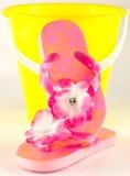Розовые темповые сальто сальто и желтое ведро песка Стоковая Фотография