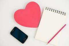 Розовые телефон и тетрадь подарочной коробки сердца на белой предпосылке Стоковые Изображения RF