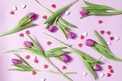 Розовые тюльпаны и сердце конфеты аранжировали в ряд на розовой предпосылке Валентайн приветствию s дня карточки Стоковое фото RF