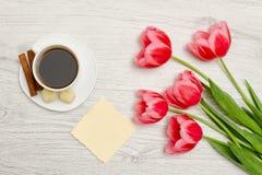Розовые тюльпаны, чистый лист бумаги, кружка кофе и cinamon, светлая деревянная предпосылка Взгляд сверху Стоковые Фотографии RF