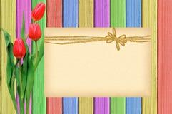 Розовые тюльпаны и карточка над затрапезным деревянным столом краски Стоковые Фото