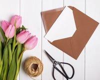 Розовые тюльпаны и конверт с пустым papr на белой деревянной плате стоковое изображение