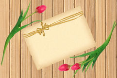 Розовые тюльпаны и поздравительная открытка над затрапезным желтым деревянным столом Стоковые Фотографии RF