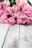 Розовые тюльпаны над затрапезным белым деревянным столом стоковое фото