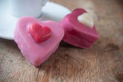 розовые форменные печенье и чашка кофе сердца на деревянном Стоковые Изображения