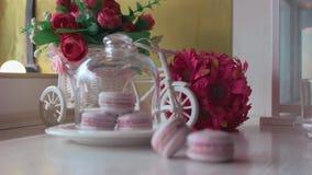 Розовые французские macarons под стеклом на деревянных досках, мягкой предпосылкой фокуса Сладкая пустыня в кафе видеоматериал