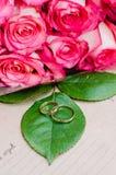 Розовые цветки роз и обручальные кольца на зеленых лист, предпосылке ремесла Стоковое Фото