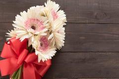 Розовые цветки gerbera в деревянной предпосылке с лентой Стоковые Фото
