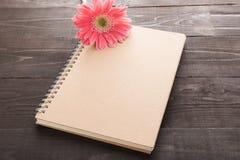 Розовые цветок и тетрадь gerbera на деревянной предпосылке Стоковые Изображения RF