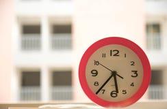Розовые часы на таблице Стоковые Изображения