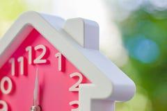 Розовые часы с домашней формой на 12 o' часы против запачканное естественного стоковая фотография