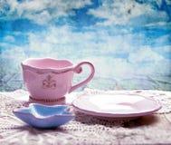 Розовые чашка, поддонник и морские звёзды сформировали шар на таблице над предпосылкой неба grunge Стоковая Фотография