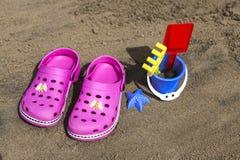 Розовые crocs пляжа и голубой песок забавляются на песчаном пляже Пристаньте темповые сальто сальто на переднем плане и запачканн Стоковая Фотография