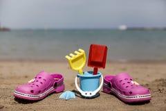 Розовые crocs пляжа и голубой песок забавляются на песчаном пляже Пристаньте темповые сальто сальто на переднем плане и запачканн Стоковая Фотография RF