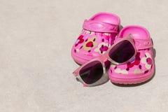 Розовые crocs/сандалии и солнечные очки ` s ребенк пляжа на песчаном пляже Стоковые Фотографии RF