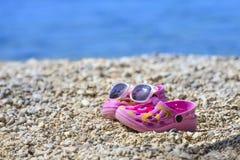 Розовые crocs/сандалии и солнечные очки ` s ребенк пляжа на песчаном пляже Стоковое Фото