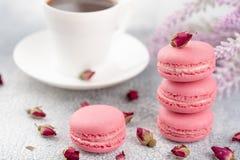 Розовые macaroons с высушенными бутонами и чашкой кофе цветка пастельно Стоковое Изображение