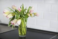 Розовый букет тюльпанов в стеклянной вазе на кухне Стоковое Изображение