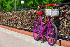 Розовый велосипед стоя на мосте влюбленности Стоковая Фотография