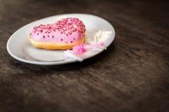 Розовый донут с замороженностью лежит на белой плите Стоковые Фотографии RF