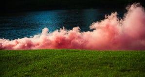 Розовый дым на зеленой траве на речной воде, спорте стоковые фотографии rf
