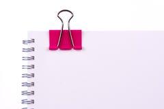 Розовый зажим связывателя на чистом листе бумаги Стоковое фото RF