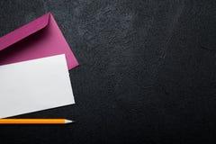 Розовый конверт, пустой белый лист бумаги и карандаш на черной предпосылке : стоковая фотография rf